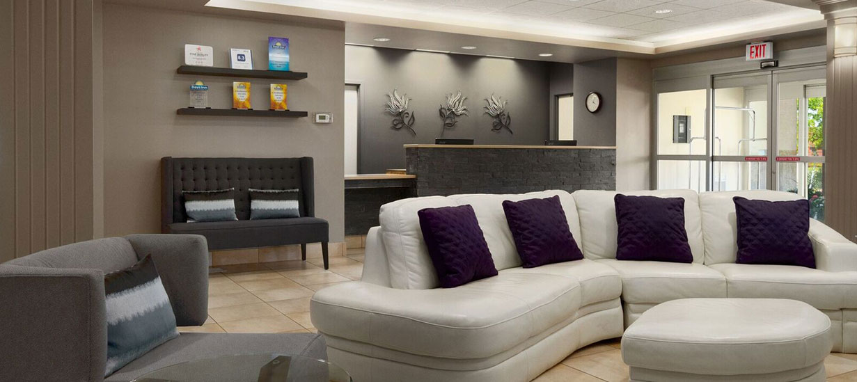The lobby of the d3h Days Inn Edmonton South hotel, is lavishly furnished with a plush curved white sectional sofa with contrasting eggplant purple accent pillows, a gray plush armchair with truncated arms, and a charcoal gray tufted upholstered loveseat that matches the tone of the stacked-stone check in counter.