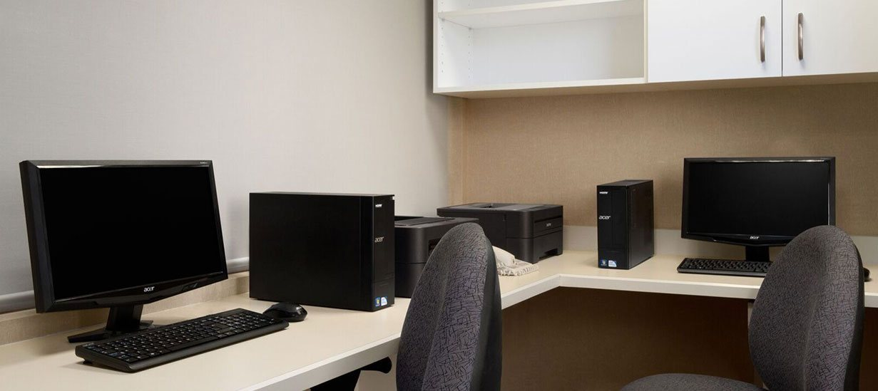 The 24-hour business centre at d3h Days Inn Edmonton South is equipped with two sets of desktop computer units with monitors, keyboards, and CPU towers and two desktop printers set on a spacious workbench.