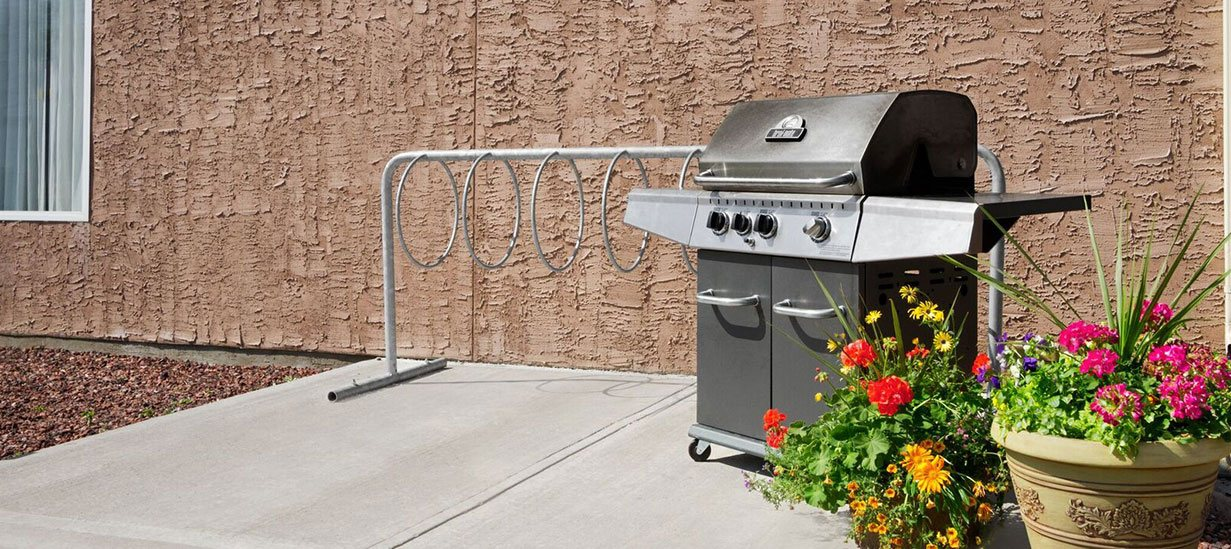 The outdoor barbecue area is in a secluded space behind the d3h Days Inn Edmonton South hotel equipped with a large full-sized stainless steel barbecue and grill station.  Two ceramic planters filled with green vegetation and multi-colored florals are placed nearby.