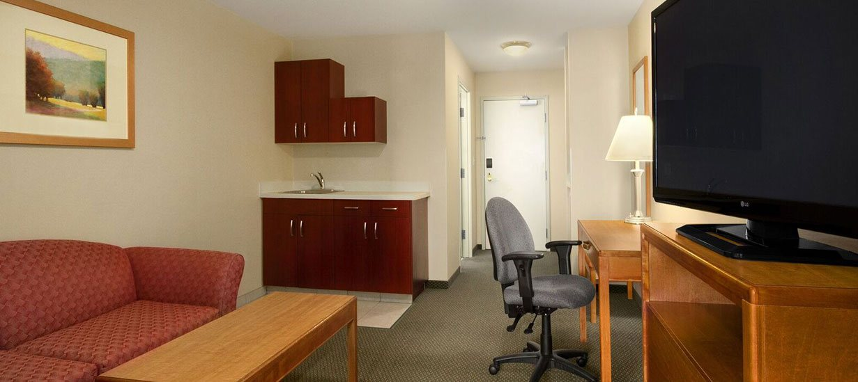 The Extended Stay Room at d3h Days Inn Edmonton South is equipped with a kitchenette and sink and furnished with a dusty rose colored loveseat, solid honey brown wood coffee table, writing desk, TV stand  and a flatscreen TV.