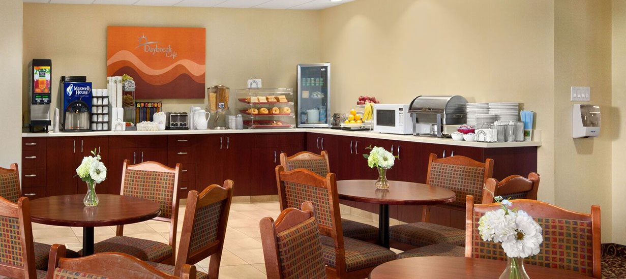 Stacks of plates, a microwave oven, toaster, countertop food warmer and mini-fridge sit atop the self-serve breakfast bar at d3h Days Inn Edmonton South, while wood round tables each surrounded by four upholstered chairs are placed throughout the Daybreak Cafe.