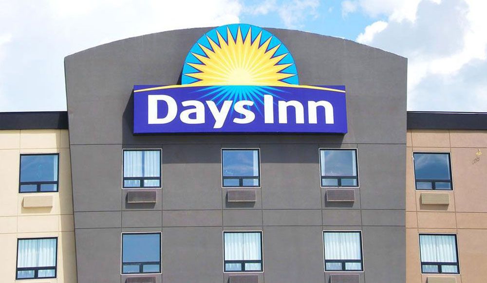 The view of the summit of the d3h Days Inn Calgary Airport hotel, with the corporate sign logo (represented by a bright yellow sunrise icon against a blue background with the corporate name in white typeset) mounted over the windows of the topmost floor of the building.