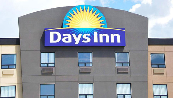 A large scale sign of the Days Inn logo is placed high atop the roof of the graphite-gray exterior of a Days Inn property.  The Days Inn corporate name is presented in bold white type, with a yellow sunrise icon contrasted against a blue background.