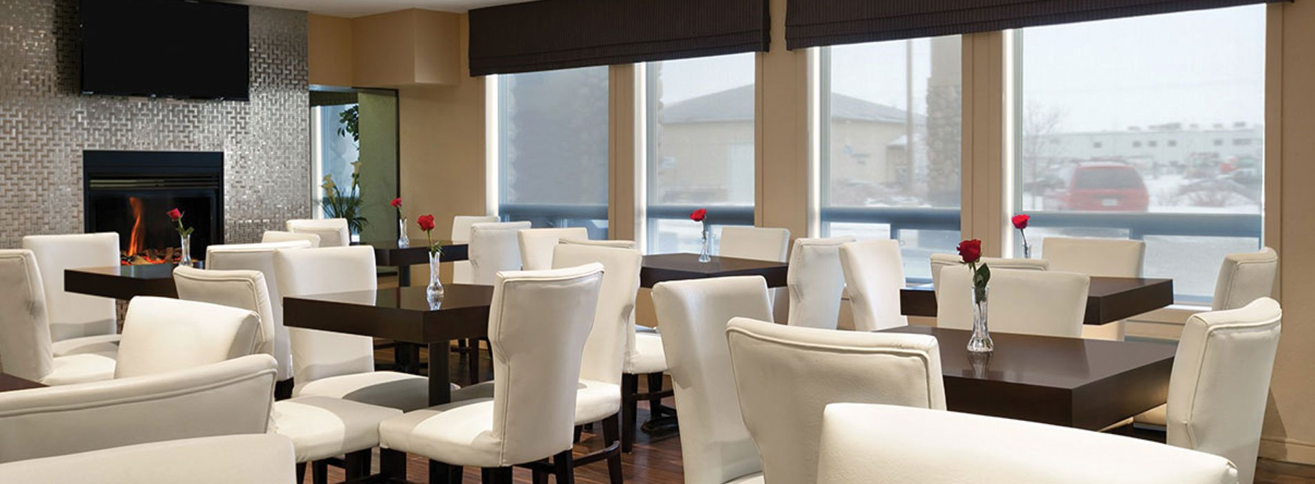 Natural light from large windows in the dining area at d3h Days Inn Regina, reflect off the shiny metallic surround of the glass enclosed fireplace, with a flatscreen TV mounted above.  Single red roses in bud vases sit atop square eating tables surrounded by white upholstered dining chairs.