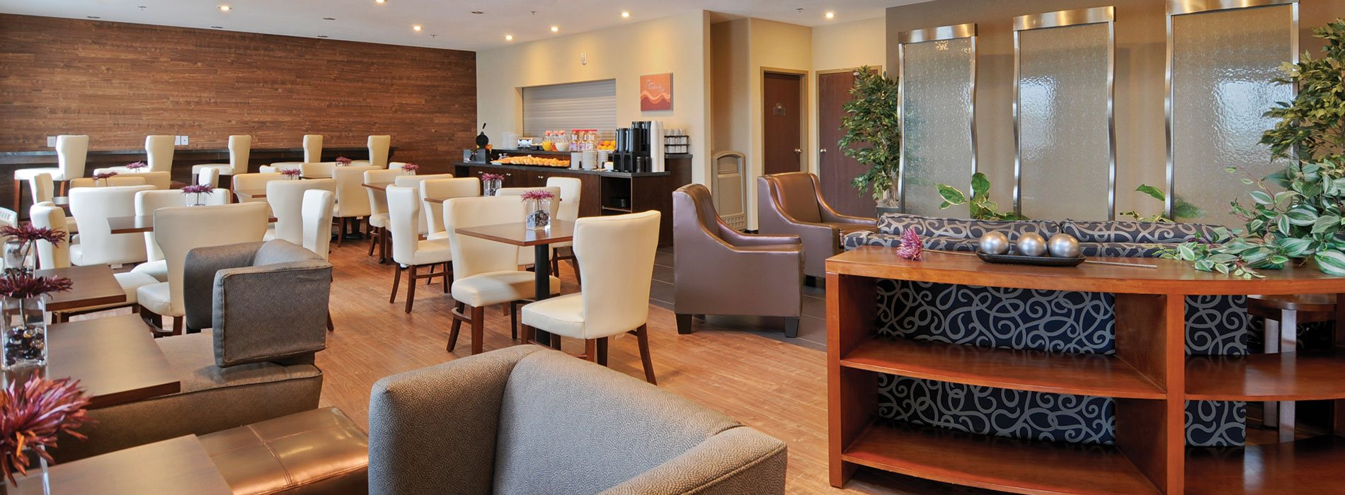 An overview of the Daybreak Café and the lounging space at d3h Days Inn Regina Airport West.  The lounge area is furnished with a swirl patterned navy blue sofa, two vinyl latte color armchairs, a sofa console table and several placements of potted green leaf plants.  The dining space features a fully stocked chocolate brown breakfast counter, a tawny brown wood paneled accent wall with built in breakfast bar and square eating tables paired with white upholstered dining chairs.