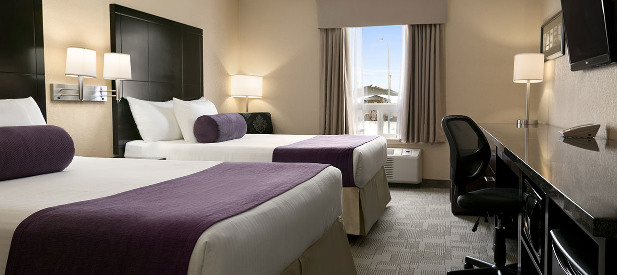 The Classic Two Queens suite includes two queen sized beds fitted with white, sand and royal purple linens complemented by tall dark charcoal gray wood headboards.  A long dark granite top work bench with black swivel chair and wall mounted flatscreen TV sit opposite the beds.  Match wall sconces and table lamp (with drum shades) provide generous lighting.