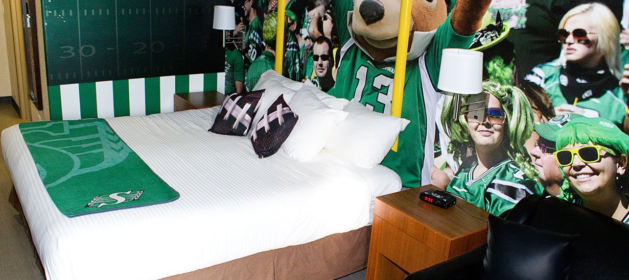 The Green & White Football Theme Room at d3h Days Inn Regina features a bed outfitted in white linen, adorned with football laced accent pillows and specialty wallpaper with images of sports fans dressed in green.  A chalkboard with football field yard markers is mounted against a white and green striped painted accent wall.