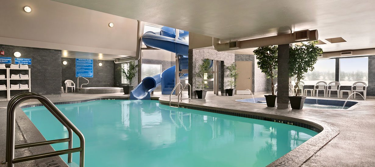 Panoramic view of the turquoise blue waters of the swimming pool of the d3h Days Inn Regina East hotel, showcasing a large blue snake shaped waterslide, circular hot tub, and water spouts surrounding a rectangular wading pool.  White plastic shelves bearing complimentary towels, white plastic patio chairs with matching side tables and potted tall plants are placed throughout the bright pool space.