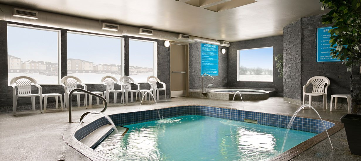 Indoor pool facilities at d3h Days Inn Regina include a round hot tub  in a private corner and a large square-shaped wading pool with blue tiling interiors.  Tall green potted plants are placed against stone slate gray walls, while white patio chairs and tables surround the shallow wading pool and water spouts.