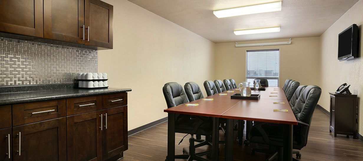 A meeting and conference room at d3h Days Inn Regina East is equipped with rows of black swivel leather office chairs placed on both sides of a long work table, wall mounted flatscreen TV, a phone placed on a small stand-alone cabinet and rich chocolate brown wood paneled kitchen cabinets with two trays of coffee cups stacked on the grey granite countertop.