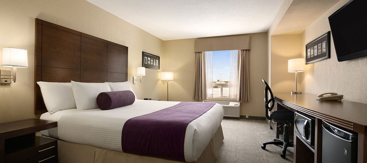 A one bed suite at d3h Days Inn Regina East is furnished with a king sized bed made up in white and eggplant purple linen, a long solid wood worktable, a swivel office chair, chestnut brown wood bedside table, and includes amenities such as flatscreen TV, mini refrigerator and microwave oven.