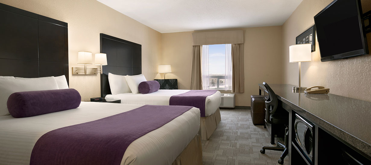 The Classic Two Queens suite at the d3h Days Inn Regina East hotel features beds fitted in white and purple linens and topped with white pillows and a cyclindrical purple bolster accent pillow.  The beds face a long dark granite topped work table with ergonomic chair and a mounted flatscreen TV on the opposite wall.