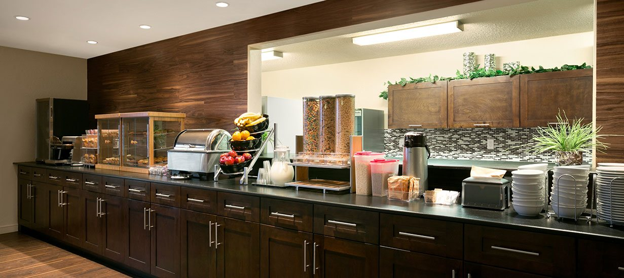 The Daybreak Café at d3h Days Inn Regina is equipped with an elongated chocolate brown wood paneled breakfast bar with a blacktop counter stocked with baked goods, cereals, bowls of fruit, beverages and amenities such as stainless steel countertop food warmer and toaster.