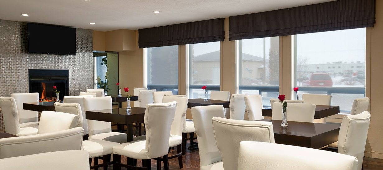 The hardwood floor dining area of d3h Days Inn Regina is brightly lit through large windows letting in natural light to reveal clusters of square wood eating tables complemented white high back dining chairs, and a silver metal geometric patterned accent wall with inset glass enclosed fireplace and flatscreen TV mounted above.