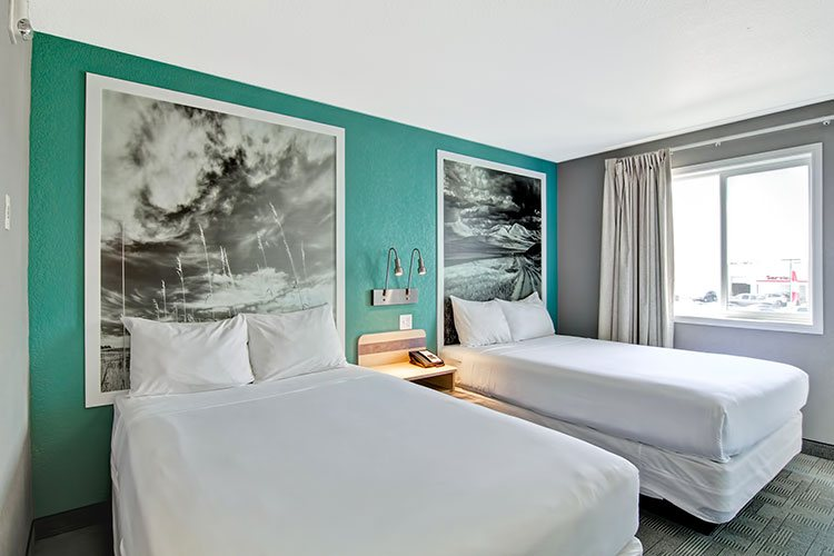 A two bed suite at d3h Home Inn Express Medicine Hat features two large framed black and white photos hanging against turquoise green walls with a large window letting in bright natural light into the room.