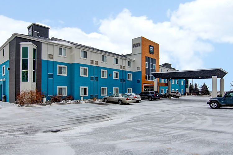 The parking lot of d3h Home Inn Express in Medicine Hat is covered with a dusting of snow with a view of the three storey hotel, painted alternately in blue, orange and white colors.