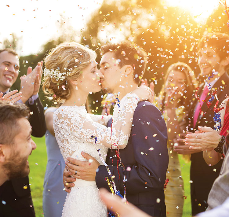A newlywed couple (the bride dressed in white lace, the groom in a blue suit) kiss as friends and family happily applaud while confetti rains down all around.
