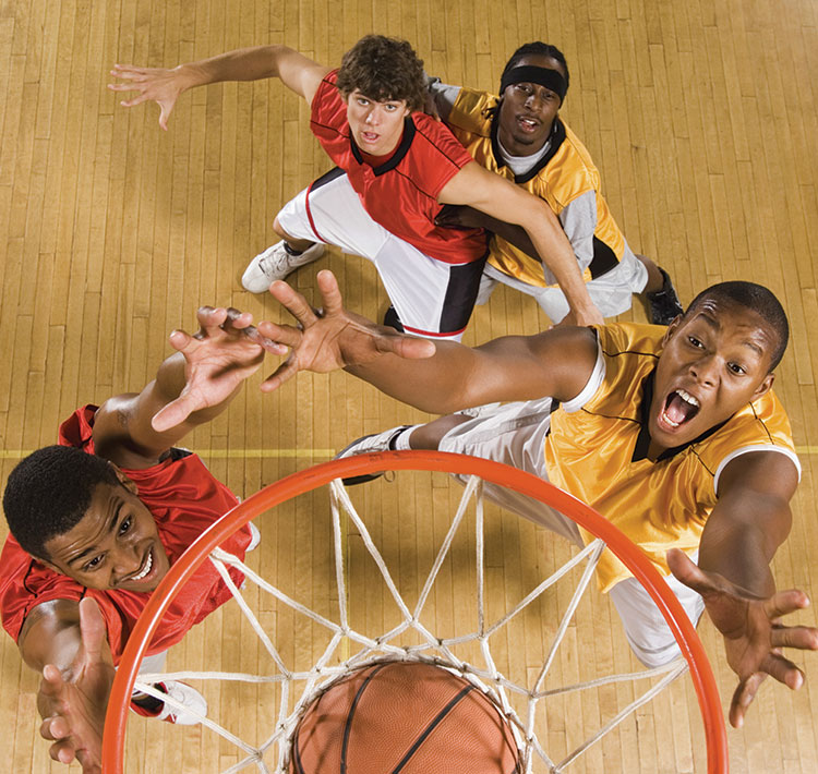 Four young males engaged in a game of basketball, stop and watch in anticipation as the ball is shot into the basket and the point is scored.