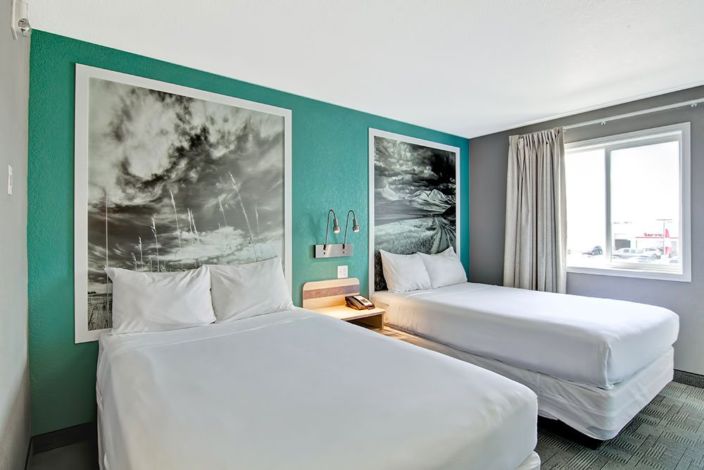 The Family Room suite at Home Inn Express in Medicine Hat features a tri-color interior: turquoise green, white and seal gray painted walls with large white framed black and white photos mounted against the walls.  Two wall mounted metal gooseneck lamps are placed between two beds dressed completely in white linen.