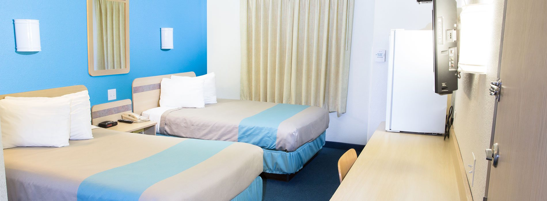 A two bed suite at d3h Motel 6 Red Deer includes beds dressed in white, light gray and powder blue linens facing a wall mounted 32-inch flatscreen TV.  Other furnishings include matching wheat color wood bedside table, and a long work bench with a white mini refrigerator sitting atop.