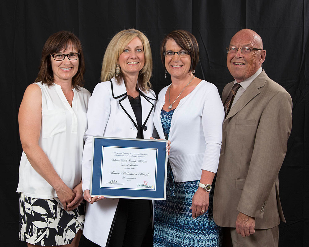 Three females and one male member of the d3h hotels human resources management team are smiling while one female team member holds up the Tourism Ambassador Award from Tourism Saskatchewan.