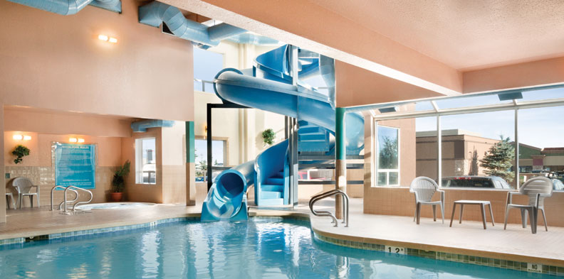 The indoor pool area at a d3h managed hotel property features a large blue serpentine water slide, plastic white patio chairs and a round shaped hot tub sequestered in a private corner with a window looking out into the parking lot.