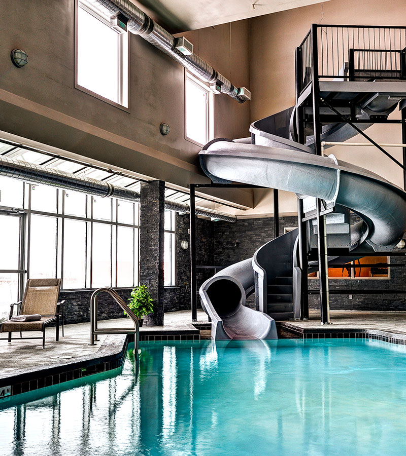 Abundant natural lighting flow in from large windows and glass doors of the indoor swimming area at d3h Home Inn & Suites Swift Current, revealing a twisting large gray waterslide meandering into the black tiled pool.  A lone wicker chaise lounge is placed by the pool's edge for spectators.
