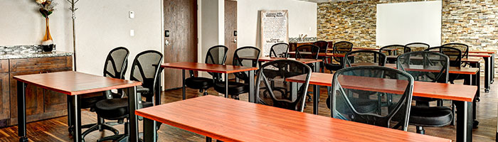 The meeting room at d3h Home Inn & Suites Swift Current features rows of ochre brown wood writing tables with two black swivel high back office chairs to a table and a whiteboard mounted up against a multicolored stone accent wall in the background.