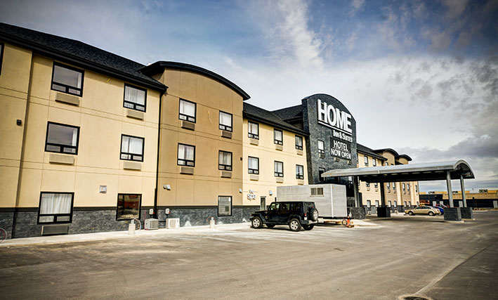 Several cars are parked near the back entrance to the d3h Home Inn & Suites Swift Current hotel, which is covered by a semi-circular portico supported by steel posts encased in a stone and concrete base.  The three storey hotel building is painted in tri-tone slate gray, cream and tan.  Above the hotel entrance, Home Inn & Suites is displayed as signage in large and prominent white lettering with an accompanying black banner beneath, announcing Hotel Now Open in bold white typset.