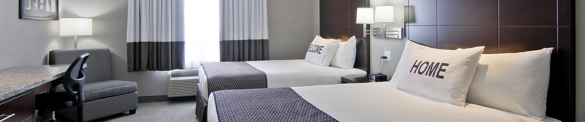 A two bed suite at d3h Home Inn & Suites Regina Airport showcases beds immaculately made up in white linen  with prominently displayed