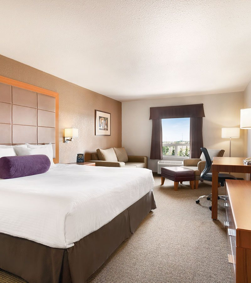 The Business Class suite at d3h Days Inn Calgary Airport features an impeccably made king bed along with a solid wood dresser, honey wood color writing table, tan armchair paired with a leather ottoman and a loveseat placed in a corner of the room.