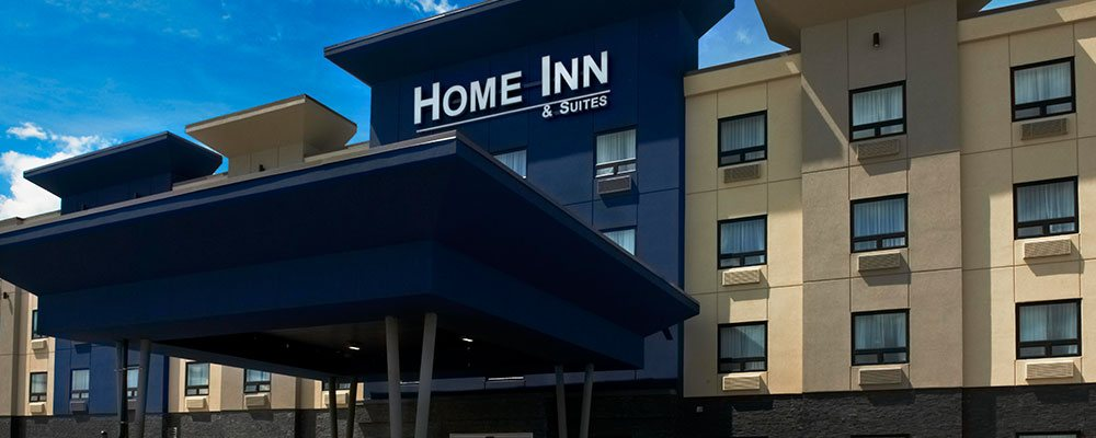 An upfront view of the flat roof navy blue portico that provides coverage over the entrance to the d3h Home Inn & Suites Saskatoon South.  The corporate name, in bold white typeset is displayed as signage high above the hotel entrance and portico.