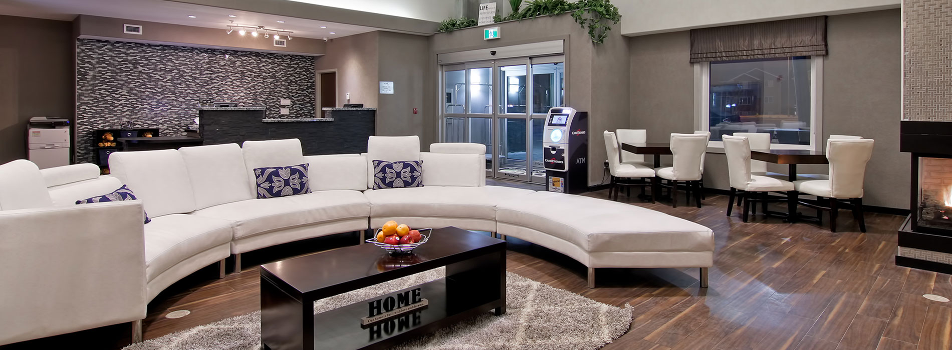 A large semi-circular white sectional sofa dominates the space in the lobby of d3h Home Inn & Suites Regina Airport.  Around the perimeter of the space is an ATM placed next to the glass door entrance and the slate gray stone check-in counter stands in stark contrast against a black, white and gray patterned accent wall.