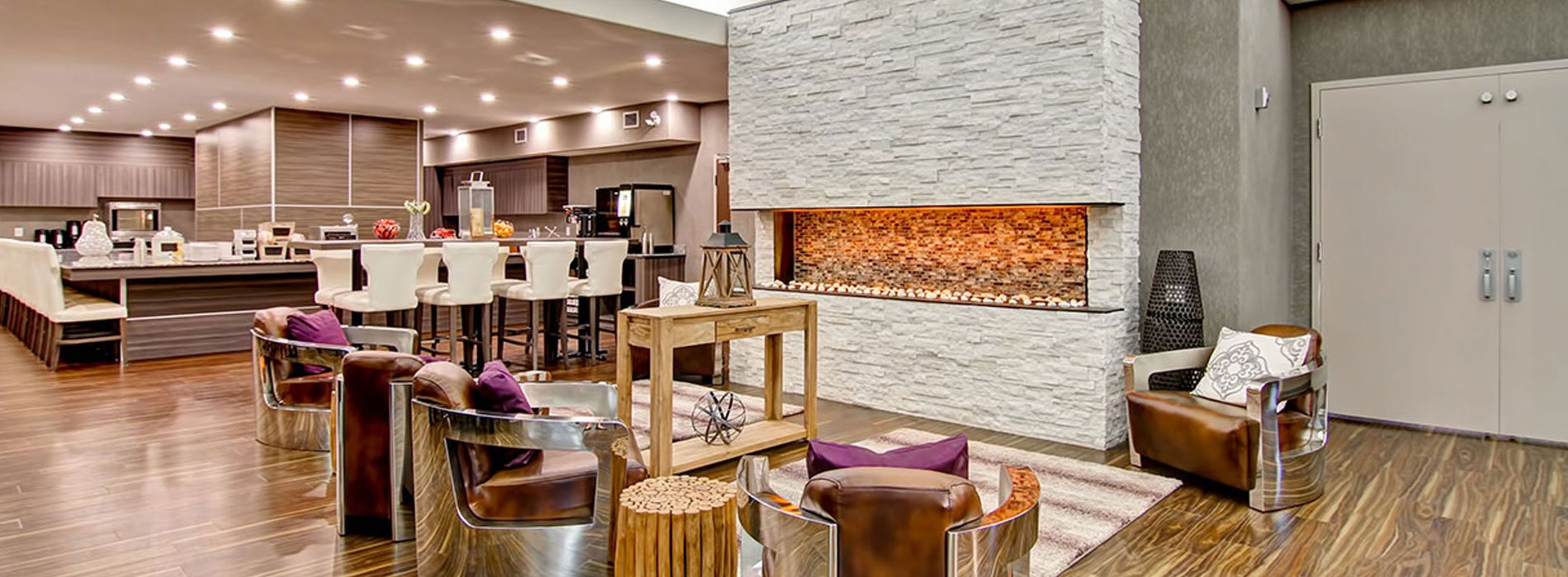 A towering birch white limestone electric fireplace is surrounded by leather club chairs, tree stump side tables, area rugs and a rustic console table bearing metal and wood décor items in the lounging space at d3h Home Inn & Suites Swift Current.  In the background, the wood grain laminate interior of the breakfast area can be seen among neat rows of white upholstered Parsons dining chairs.
