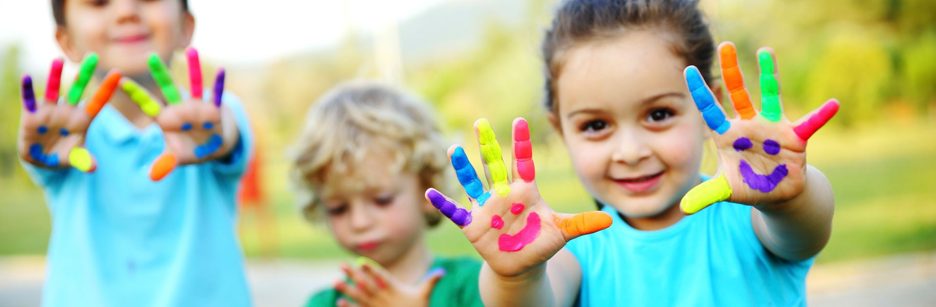 A photo promoting corporate social responsibility initiatives of d3h hotels, particularly works with childrens' charities:  Two young children are cheerily holding out both pairs of hands with fingers smeared in multi colors and happy faces painted on palms.  In the background a younger child looks curiously down at his own painted covered hands.