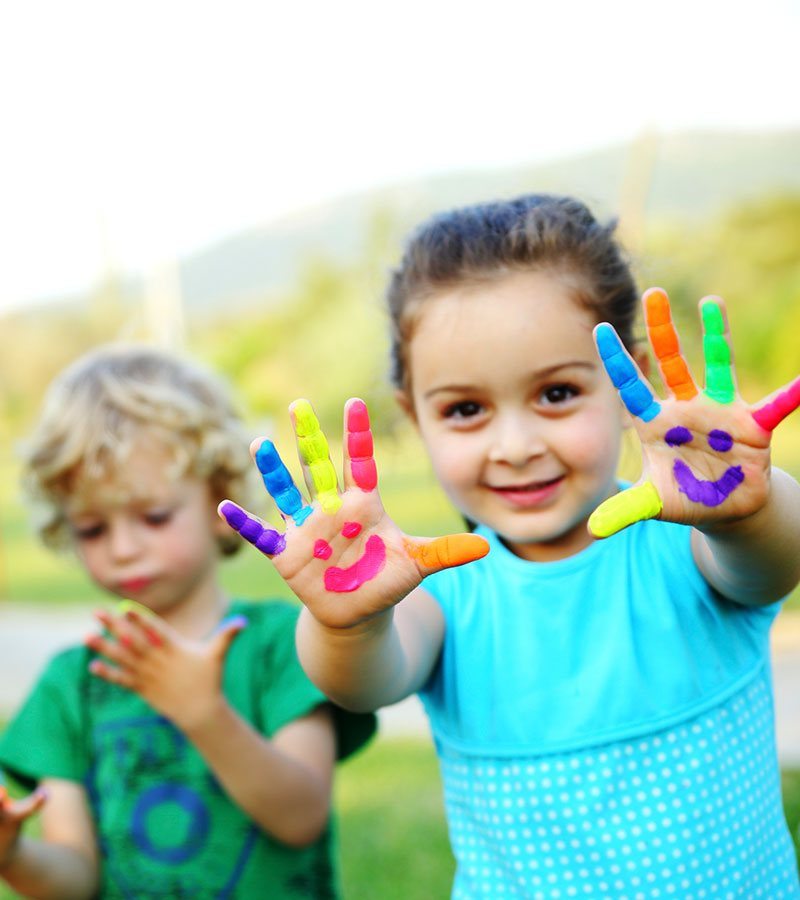 A young girl is eagerly and happily holding up her fingers painted in bright multiple colors with palms painted with a happy face, while in the background a younger blond male child stares contemplatively at his own painted hands.