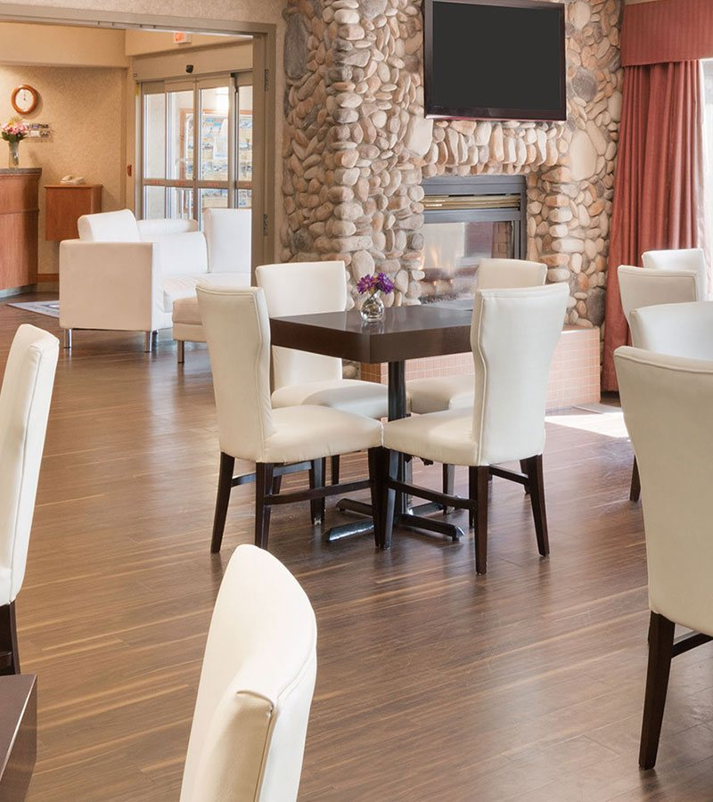 Modern and traditional furnishings can be found in the dining and lounge space at a d3h managed hotel property.  Traditional elements include: an  elongated breakfast counter with mahogany cabinetry, white upholstered Parsons chairs form a dining set with dark wood eating tables and white high back tufted upholstered armchairs with black arm trim.  Modern touches are seen in white cube shaped ottoman seating, a bright silver herringbone pattern surround fireplace and a black and white pattern accent wall at the back of the dining area.