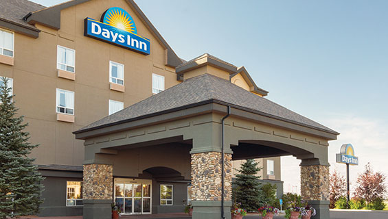 Two tall spruce trees are placed by a concrete and stone portico built over the glass door entry to d3h Days Inn Medicine Hat in Alberta.  At the top of the triangular roof of the hotel, the Days Inn corporate logo, presented in white lettering and yellow sunrise icon set against a blue background, is displayed over the entrance.