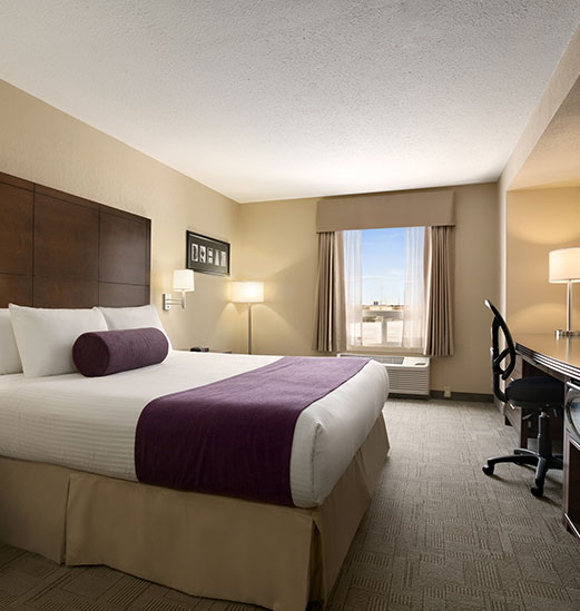 A king sized bed dressed in white, beige and purple linens from the d3h Signature line, faces an opposing wall against which rests a solid dark granite topped workspace paired with a black swivel ergonomic chair at the d3h Days Inn Regina hotel in Saskatchewan.