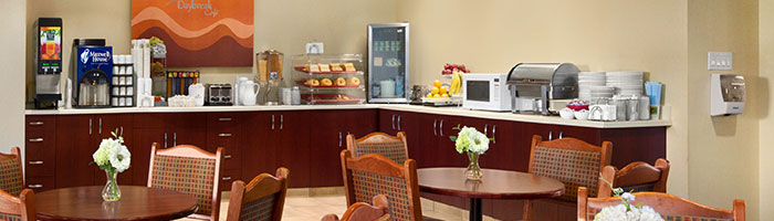 The Daybreak Café breakfast bar is stocked with baked goods, fruit, beverages, condiments, and cereals, with amenities such as microwave oven, toaster and countertop food warmer at the d3h Days Inn Edmonton South hotel.