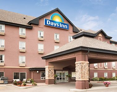 A small photo of the parking lot entrance to the d3h Days Inn Calgary Airport hotel, a four storey light terracotta building with the Days Inn yellow sunrise and blue background corporate logo placed at the triangular summit of the hotel.  A large concrete portico with stone accents and triangular shaped roof provides coverage over the glass door entrance.