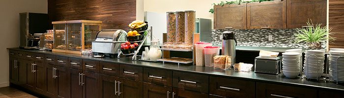 A small view of the Daybreak Café complimentary breakfast bar at d3h Days Inn Regina showcasing the long breakfast counter laden with stacks of bowls and plates, a toaster, a food warmer, plastic containers of cereals, bowls of fruit, a milk pitcher, and display cases of baked goods.