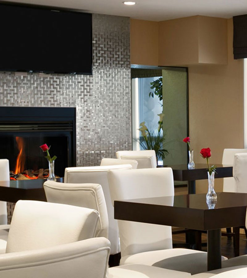 A view of the glass enclosed electric fireplace with a silver metal geometric pattern wall surround and mounted flatscreen TV in the dining area at d3h Days Inn Regina East in Saskatchewan.   White upholstered dining chairs are paired up with dark square eating tables each topped with a single rose in a vase.