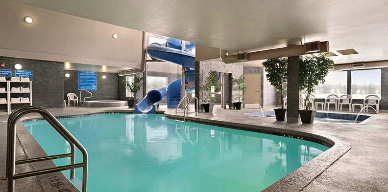 The indoor pool area at the d3h Days Inn Regina East hotel includes many amenities such as a large swirling blue waterslide descending into a rectangular shaped swimming pool, a round hot tub in a corner and a shallow wading pool.
