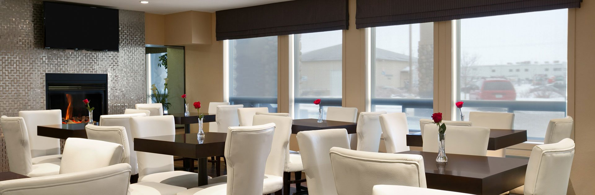 Four large windows let natural light into the dining space of d3h Days Inn Regina populated with square penny brown wood tables, topped with a single red rose in a glass bud vase, amidst a sea of white upholstered dining chairs.  The eating space is dominated by the glass enclosed fireplace with a shiny silver metallic surround and a flatscreen TV mounted above.