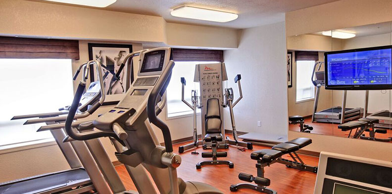 The fully equipped 24-hour fitness centre at d3h HomeSuites Regina East features free motion treadmills, elliptical machines, bicycles with built-in TVs and a weight bench.  The bright space also features hardwood floors and amenities such as a large wall mirror and flatscreen TV.