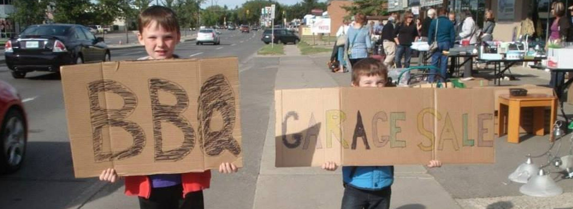 Two young children are holding up cardboard signs written out in crayon advertising the d3h BBQ and Garage Sale Fundraiser while a group of adults are looking over merchandise for sale set out on outdoor kiosks.