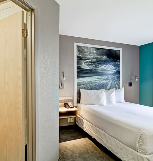 The Guest Room at the d3h Home Inn Express in Medicine Hat presents a double bed dressed entirely in white linen, a large black and white framed photo hung against a gray wall, contrasted against an adjacent turquoise green accent wall and a white painted ceiling.