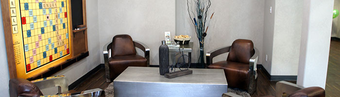A small view of the lounge and recreation space at d3h Home Inn Express Medicine Hat featuring a large wall mounted Scrabble board with attached blackboard for score keeping.  Other furnishings in the space include four leather club chairs with thick silver arms, placed among matching stainless steel top coffee and end tables.