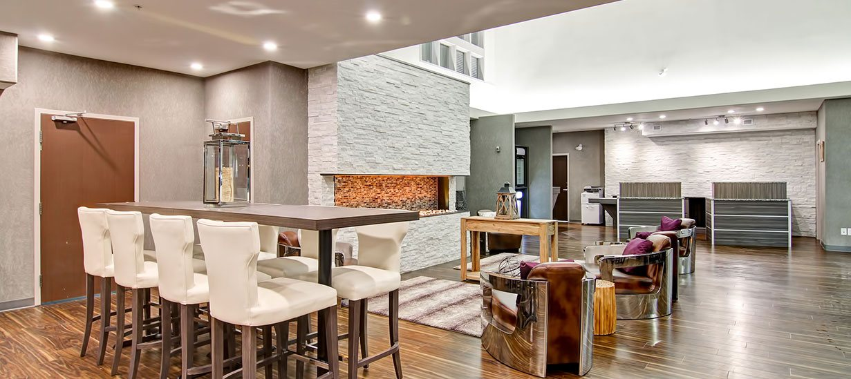 A long dining bench surrounded by white upholstered Parsons dining chairs overlooks the view of wood grain laminate check-in counters and the lounging space with leather club chairs encircling a majestic white stacked limestone electric fireplace at d3h Home Inn & Suites Saskatoon South.